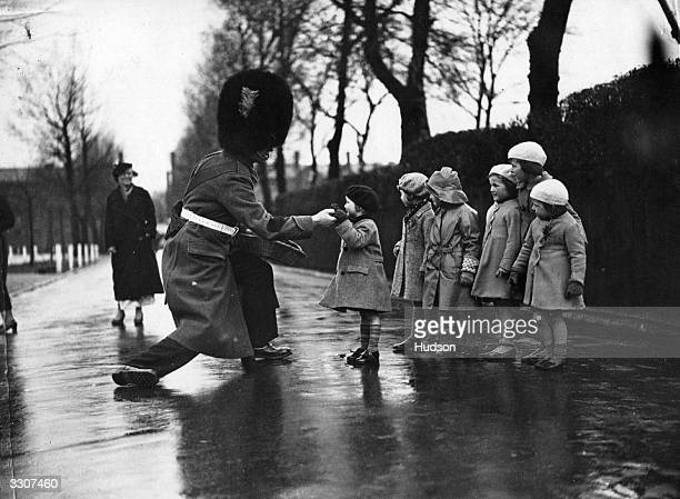 Guardsman giving pieces of shamrock to soldiers' children after the St Patrick Day's ceremony at the Irish Guards' depot in Caterham, Surrey.