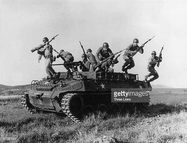 American soldiers leaping from an armoured personnel carrier during exercises in Korea.