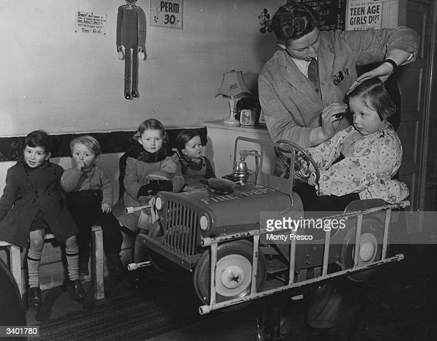 Young Monica de Witt sitting in a jeep while the barber cuts her hair at a Stoke Newington barber shop London