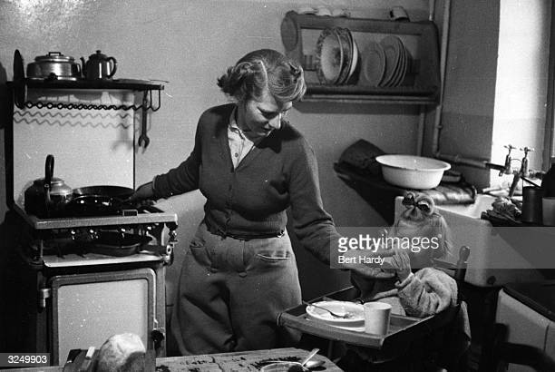 A housewife cooking dinner and feeding the baby in its high chair Original Publication Picture Post 8303 Shadow Over The Small Farm pub 1958