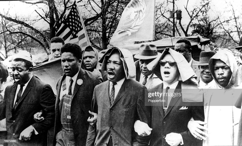 17th March 1965. Rev. Martin Luther King has his arms locked and singing as he leads a protest march to the racecourse in Montgomery, Alabama. : News Photo