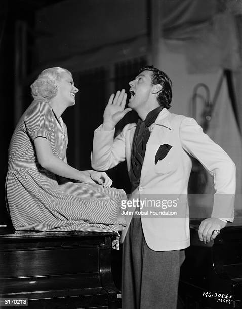 MGM star Jean Harlow watches former Olympic athlete turned film star Johnny Weissmuller do his 'Tarzan' call They are relaxing during the shooting of...