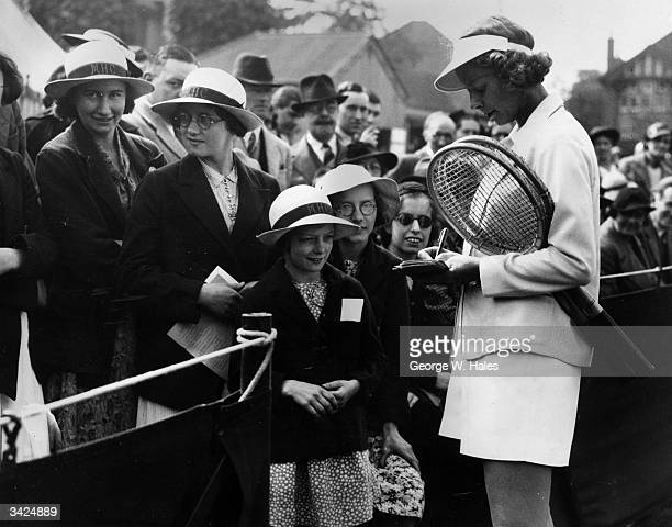 American tennis player Alice Marble signing autographs for young fans at the Surrey Grass Courts Championships in Surbiton