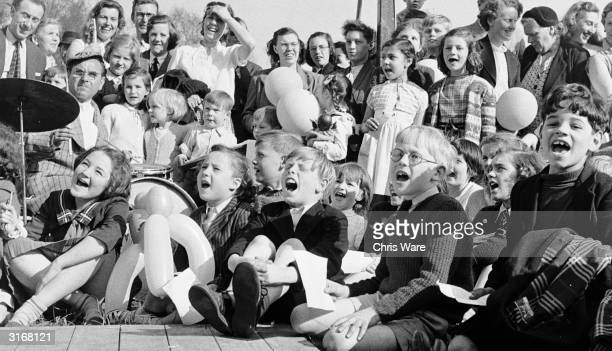 On Hampstead Heath London watched by their parents a group of children clutching balloons shout their appreciation of a live outdoor television...