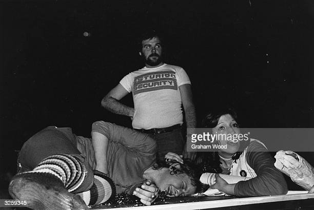 A young fan lies crying on the stage of the Hammersmith Odeon London comforted by a friend at a concert by the British rock group Slade A security...