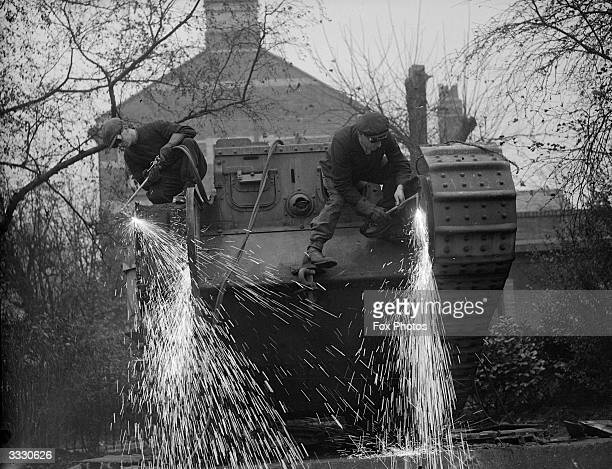 Men at work using oxyacetylene cutters to dismantle the tank given to the borough of Newport south Wales at the end of World War I The tank will be...