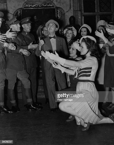 British comedian Lupino Lane and his chorus girls entertain a gathering of Army and Air Force servicemen at Victoria Palace London with their...