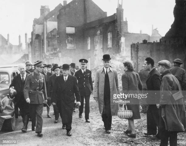 His Majesty King George VI and Herbert Morrison the home secretary and minister of home security inspect airraid damage in wartime Coventry They are...