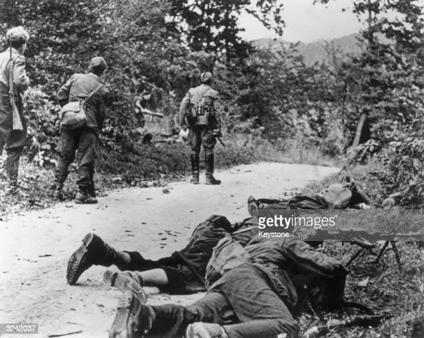 A group of Yugoslav patriot soldiers nearing a German garrison at the Litija bridge in occupied Slovenia deploy on both sides of a woodland road to...