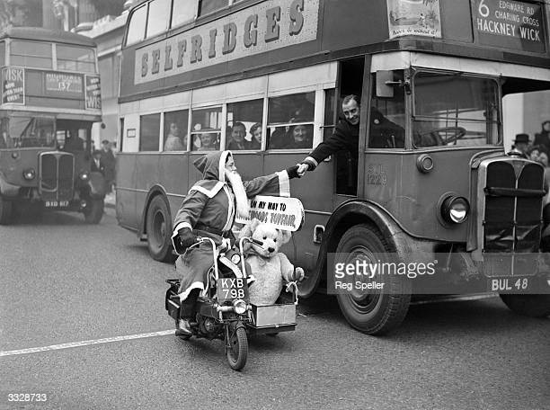 A London bus driver leans out of his cab to shake hands with Father Christmas who is passing by on his scooter