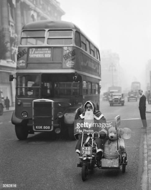 Santa Claus rides a motorbike with a sidecar down Oxford Street London
