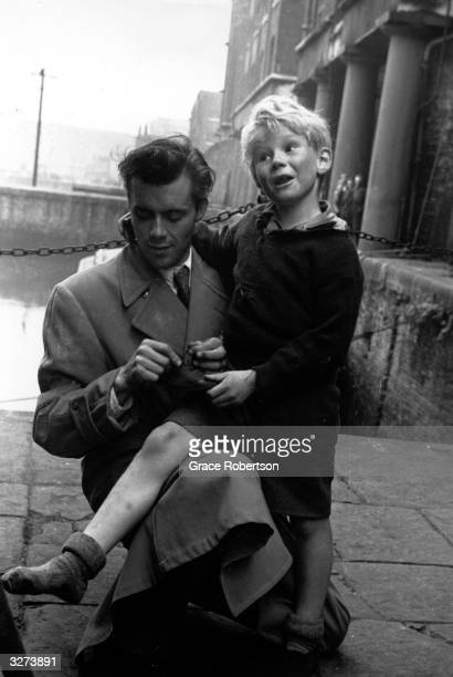 Dirk Bogarde helps child actor Jon Whiteley with his shoes during the filming of 'Hunted' directed by Charles Crichton for GFD/Independent Artists...