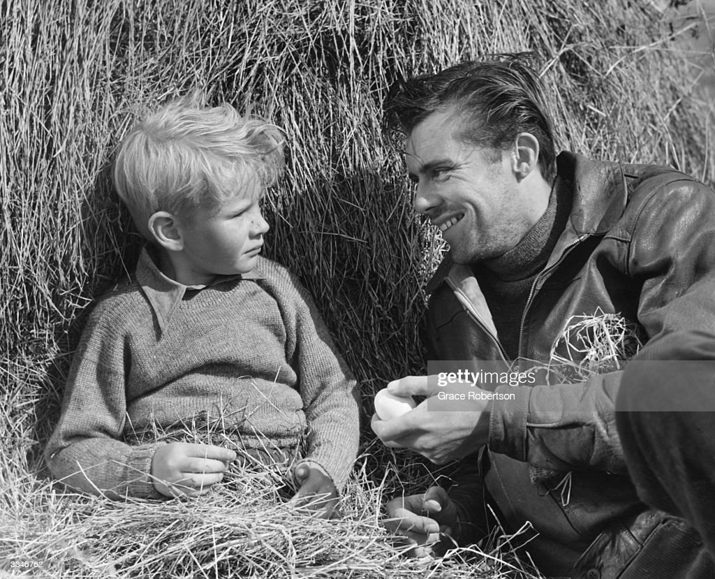 British actor Dirk Bogarde (1921 - 1999) sitting in a pile of hay with child actor Jon Whiteley during a scene from the film production 'Hunted'. Original Publication: Picture Post - 5585 - Britain's Boy Star Is A Natural - pub . 1952