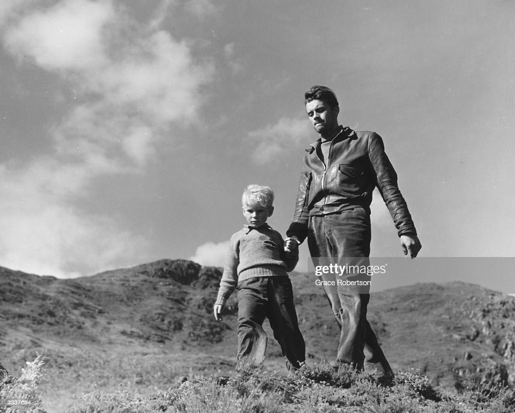 British actor Dirk Bogarde (1921 - 1999) walking on a moor with child actor Jon Whiteley during a scene from the film 'Hunted'. Original Publication: Picture Post - 5585 - Britain's Boy Star Is A Natural - pub . 1952