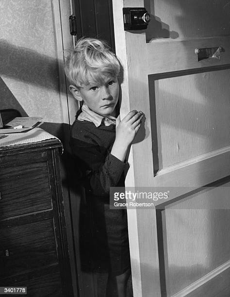 British child actor Jon Whiteley peering out from behind a door in a scene from the film 'Hunted' Original Publication Picture Post 5585 Britain's...
