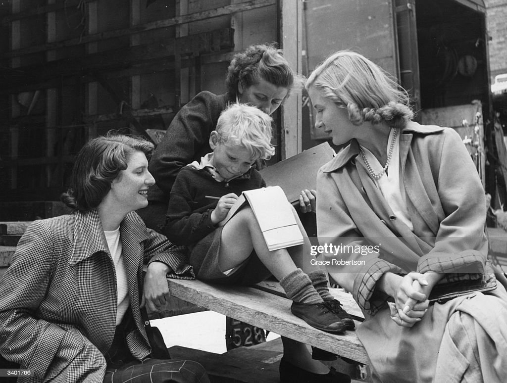 British child actor Jon Whiteley sketching in front of an admiring audience, on the set of the film, 'Hunted'. Original Publication: Picture Post - 5585 - Britain's Boy Star Is A Natural - pub . 1952