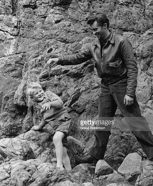 British film actor Dirk Bogarde frightens child actor Jon Whiteley with a piece of seaweed on the set of the film 'Hunted' Original Publication...