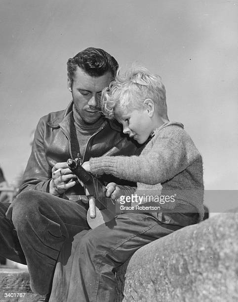 British film actor Dirk Bogarde inspects a toy gun with child actor Jon Whiteley on the set of the film 'Hunted' Original Publication Picture Post...