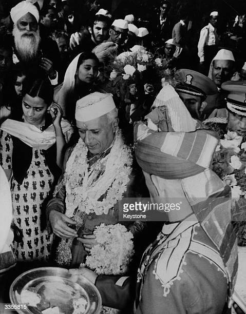 Jawaharlal Nehru , the first Prime Minister of India, celebrating his 66th birthday and receiving floral garlands at his New Delhi home.