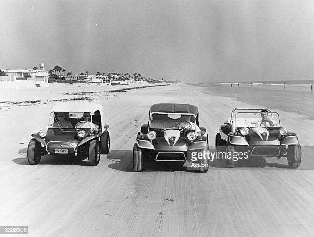 Three dune buggies designed for rugged travel over sand dunes racing on Daytona Beach Florida where the sand is unique for driving on being the most...