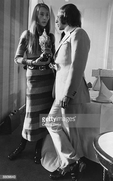 Mrs Nina Rindt receiving the racing driver's trophy from Scottish racing driver Jackie Stewart on behalf of her husband Austrian driver Jochen Rindt...