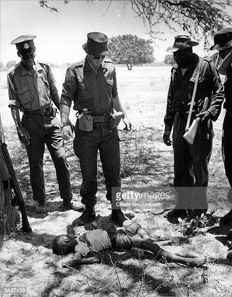 Soldiers stare down at the body of a young Angolan refugee at the camp in Ovambo during the conflict between the UNITA rebels and the MPLA