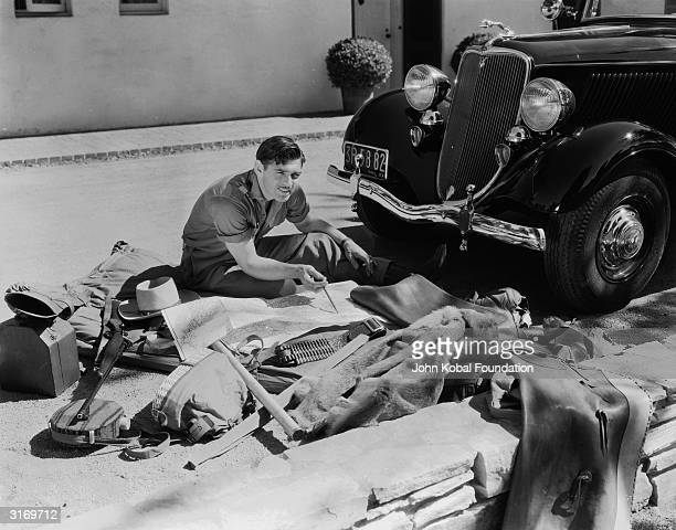 American actor Clark Gable sitting in front of his car planning his journey with a map in front of him and his travelling gear strewn around him