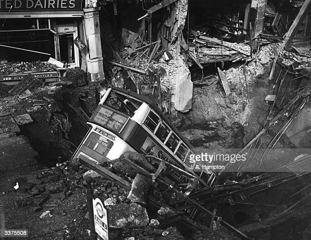 Bus in a bomb crater caused by a recent air raid on Balham in South London.