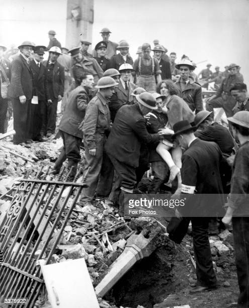 Betty Warboy being lifted to safety from the ruins of Dame Owen school in Islington North London which was hit by a bomb during a raid