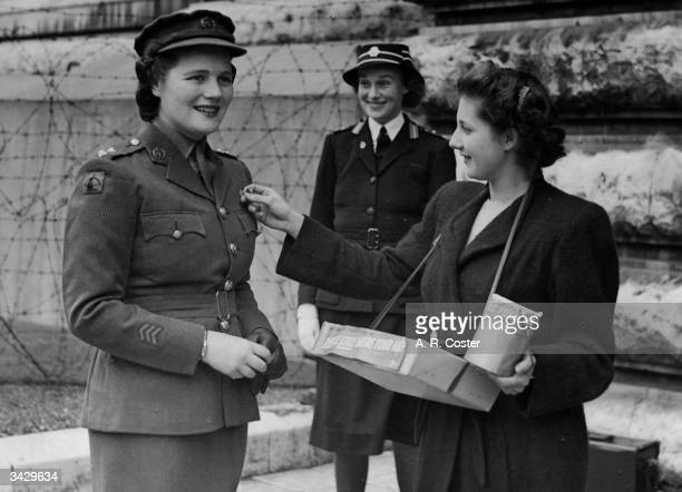 In ATS uniform Mary Churchill daughter of Winston Churchill buys a flag from Nurse Grover of University College Hospital