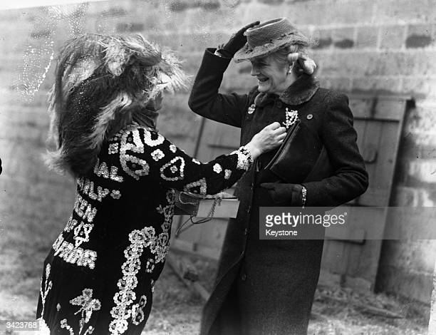 Mrs Tinsley a Pearly Queen from Blackfriars pinning a flag to Lady Churchill on 'Aid To Russia' day