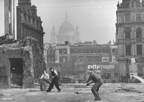 A group of men playing cricket on a blitzed site in Blackfriars London during their lunchhour with St Paul's Cathedral in the background