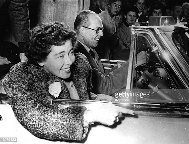 Queen Frederika of Greece , seen with King Paul driving their car in Munich.