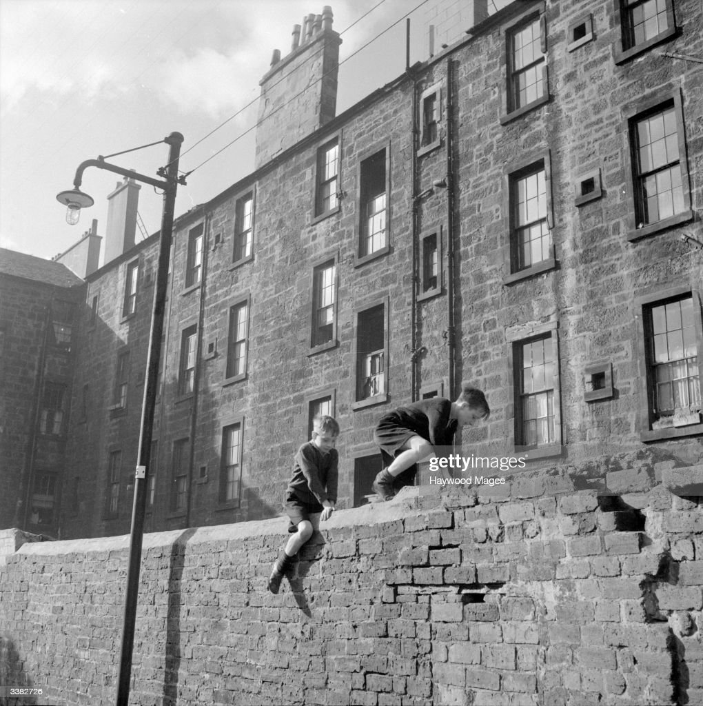 Two young boys climb over a wall backing onto a row of tenements in Glasgow, Scotland. Glasgow has over one million inhabitants which means there is always a high demand for housing and many residents have to live in tenements or sub-standard accommodation. The city is also responsible for more than half the country's industrial output and so many new residents are attracted to the area because there are good employment prospects. Original Publication: Picture Post - 6754 - Glasgow: How A City Is Run - pub. 1953