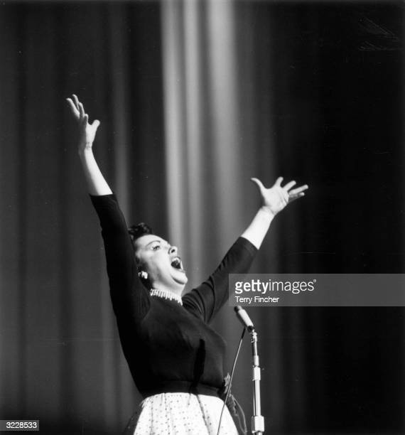 American film star and entertainer Judy Garland performing on stage at the Dominion Theatre in London