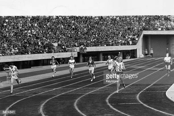 Betty Cuthbert of Australia crosses the finish line to win the 400 metres final at the 1964 Tokyo Olympics Ann Packer of Great Britain won the silver...