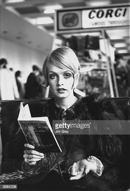 British model Twiggy reading a guide book to Tokyo at London Airport before departing for Japan where she will be modelling a fashion collection