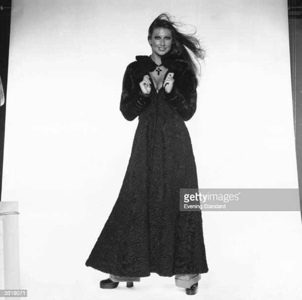 Model Marilyn Cole modelling a full-length coat.