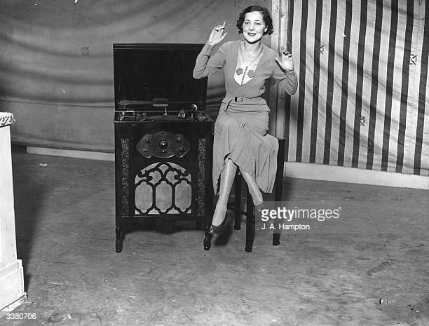 A woman demonstrating the Fullotone fourvalve radiogramophone at the Radio Olympia exhibition in London the cheapest set at 16 guineas