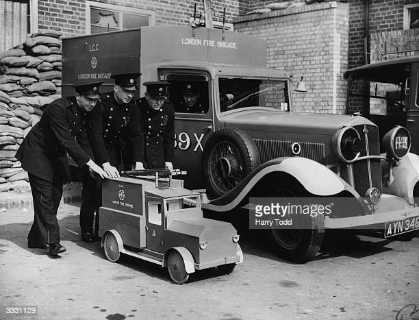 A model fire tender made by members of the London AFS from bomb debris is shown alongside the real thing