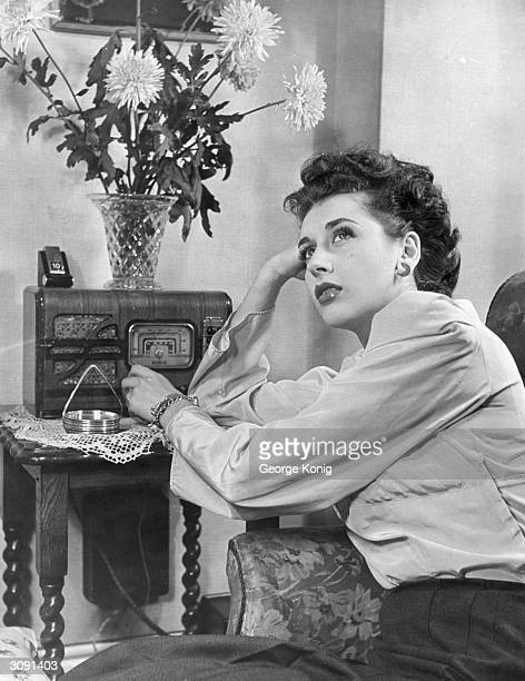 Actress Kay Kendall listening to a Promenades concert on the radio