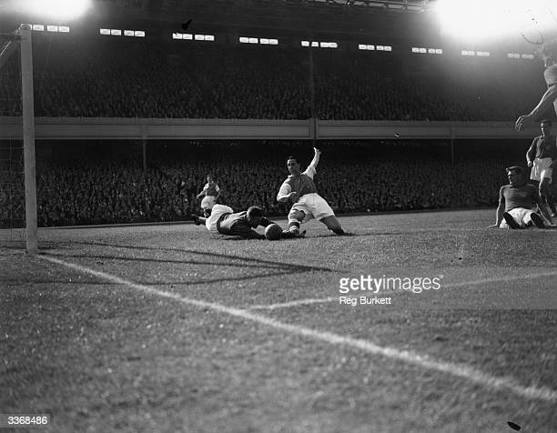 Arsenal striker Tommy Lawton competes for the ball with Portsmouth goal keeper Uprichard at Highbury