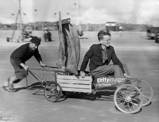 James Simpson giving Michael Woods a push start in 'Genevieve' a land yacht built from old pram wheels spare parts and with a raincoat for a sail...