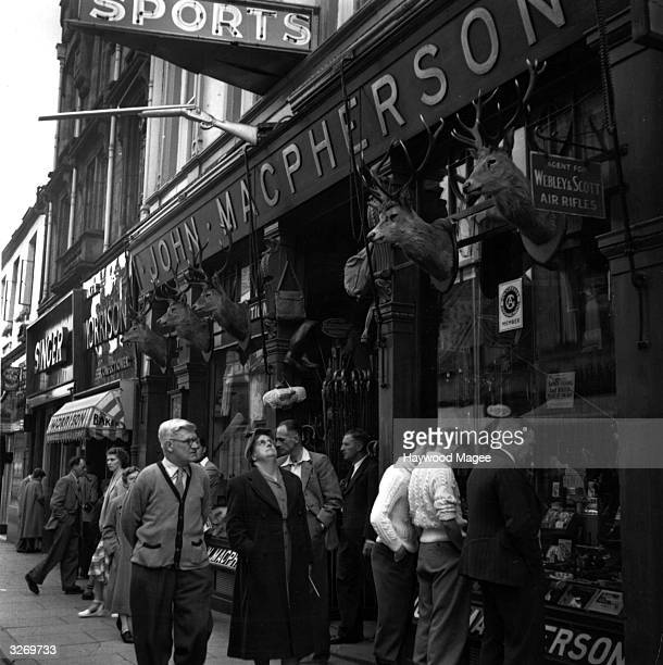 Shoppers outside John MacPherson's sporting shop in Inglis Street Inverness which is adorned with an array of trophies Many shops such as this sell...