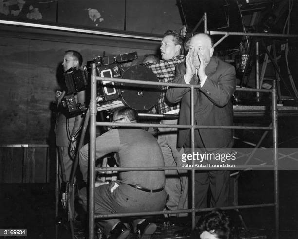 British director Alfred Hitchcock shouting instructions during the filming of a scene for 'North by Northwest' at LaSalle Street Station Chicago