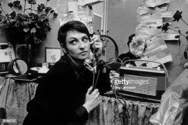 French singer Barbara listens to a radio on headphones in her dressing room which is decorated with flowers and telegrams are pinned to the wall