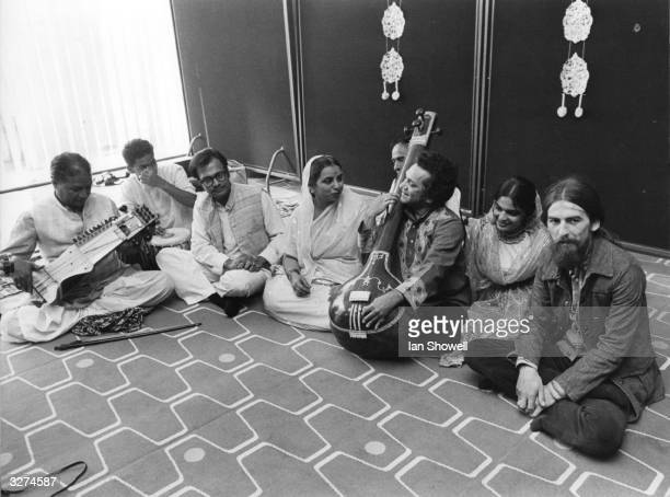 British pop musician George Harrison with a company of seven top Indian instrumentalists singers and dancers including Ravi Shankar at a press...