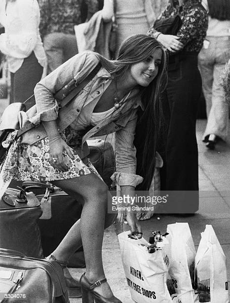A passenger at Luton Airport carrying her bags of Duty Free Shopping