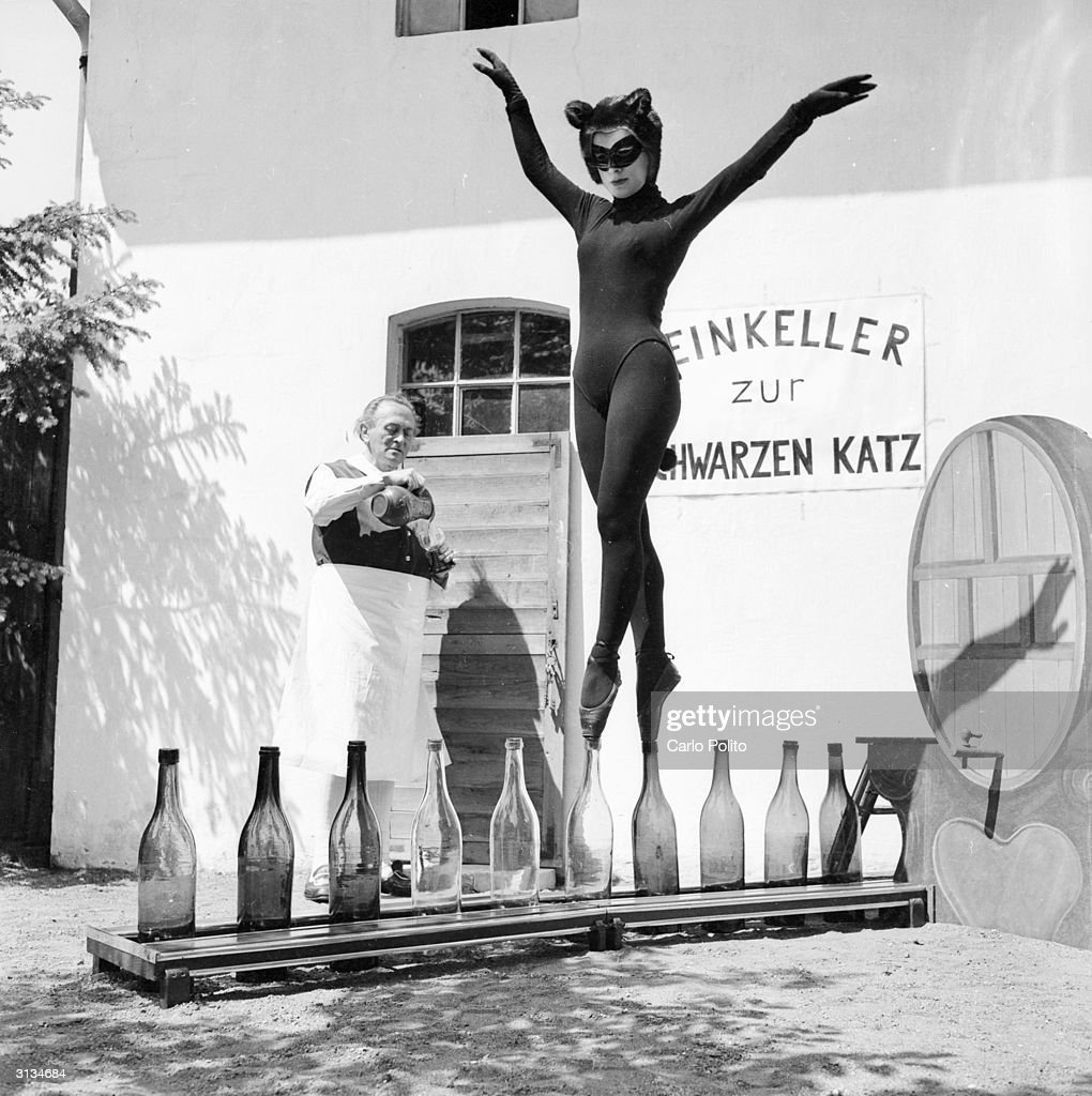 17-year-old Bianca Passarge of Hamburg dresses up as a cat, complete with furry tail, and dances on wine bottles, June 1958. Her performance is based on a dream and she practices for eight hours every day in order to perfect her dance.