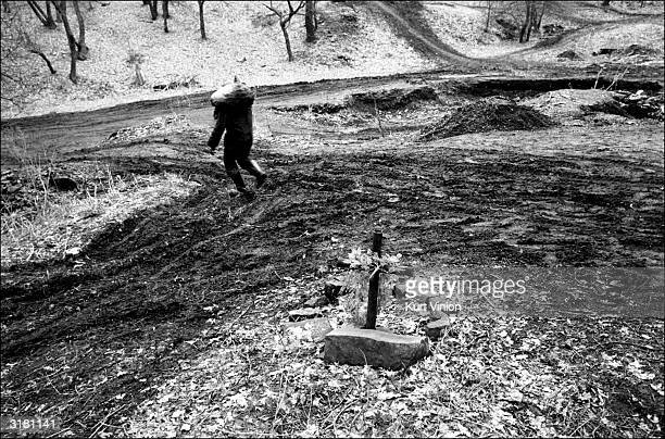 A 17yearold makes the difficult uphill journey with a 100pound bag of coal on his back as a memorial to a friend stands nearby February 25 2002 near...
